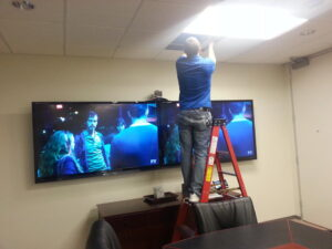 setting up dual Television display and web conference camera in meeting room
