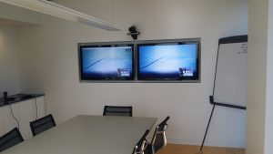 side by side tv and web conference camera in board room